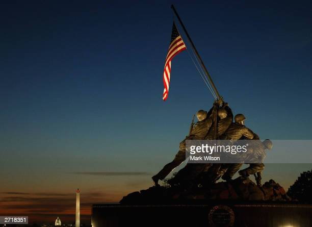The early morning sun begins to rise behind the Iwo Jima Memorial November 11 2003 in Arlington Virginia Many Veterans Day events will take place in...