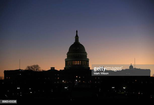 The early morning sun begins to rise behind the US Capitol as Congressional law makers work on a deal to fund the government to avert a shutdown by...