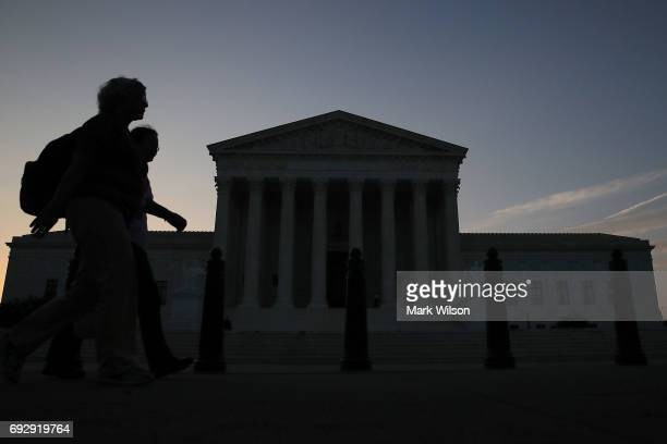 The early morning sun begins to rise behind the US Supreme Court building on June 6 2017 in Washington DC The high court could rule within days on...