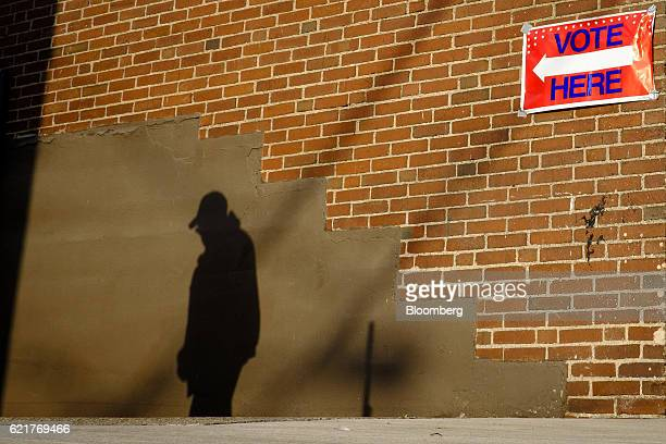 The early morning sun casts the shadow of a voter on a wall as he arrives at a polling location in Aliquippa Pennsylvania US on Tuesday Nov 8 2016...