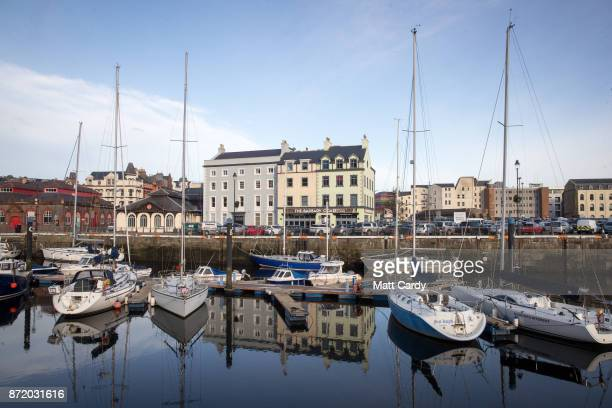The early morning sun illuminates boats moored in the harbour in the town of Douglas on November 8 2017 in Douglas Isle of Man The Isle of Man is a...