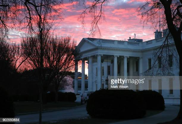 The early morning sun lights up the sky over the White House on January 8 2018 in Washington DC Later today President Donald Trump will travel to...