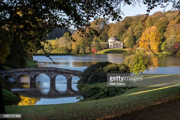 The early morning sun shines on trees that are displaying their autumn colours surrounding the Palladian bridge and the lakeside Pantheon at the...
