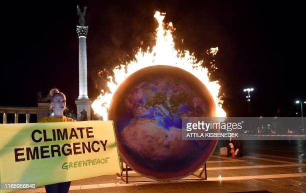 The Earth on fire is seen during a Greenpeace protest at the Heroes square in Budapest on September 4 2019