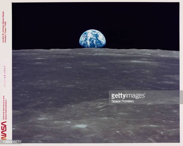 The Earth rises above the Moon's horizon, the lunar terrain is in the area of Mare Smythii on the nearside, in an image taken by Apollo 11, July...