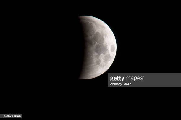 The Earth's shadow begins to fall on the surface of the moon during the partial eclipse phase of the lunar eclipse on January 21 2019 in Manchester...