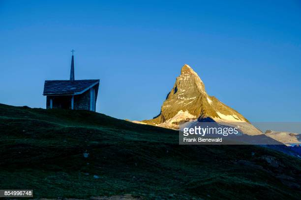ZERMATT VALAIS SWITZERLAND The East and North Face of the Matterhorn Monte Cervino at sunrise behind the small Chapel Bruder Klaus