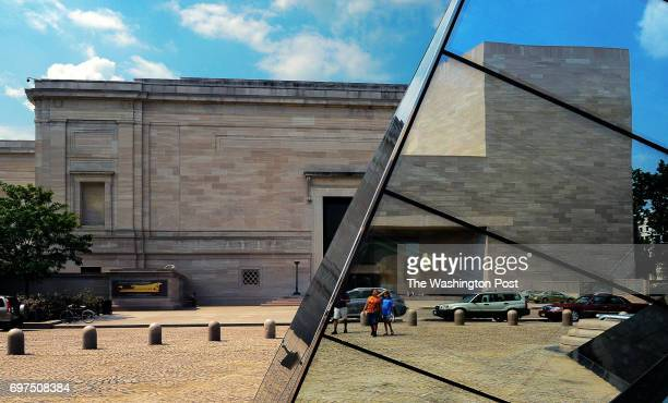 The east building of the National Gallery of Art is pictured in reflection right of one of architect IM Pei's mirrored pyramids on the plaza in front...
