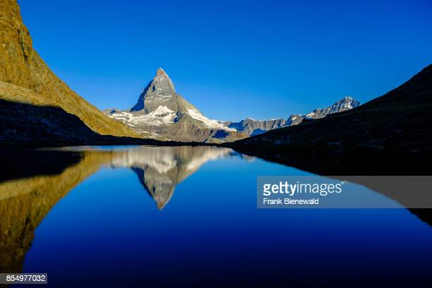 ZERMATT VALAIS SWITZERLAND The East Face of the Matterhorn Monte Cervino mirroring in the Lake Riffelsee at sunrise