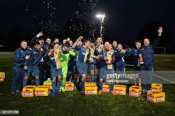 The East Kilbride players and staff celebrate with beer presented by Ajax club officials after winning there 27th game against BSC Glasgow FC during...