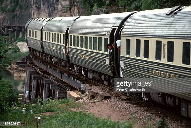 The Eastern and Oriental Express train crosses a woodtresseled bridge that cuts along the steep cliffs of the Kwai river near the famous Bridge Over...