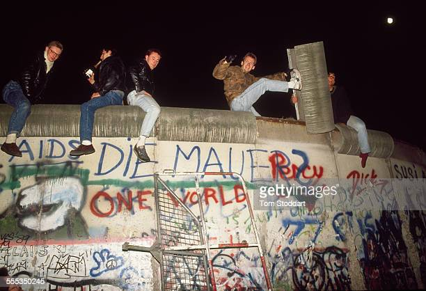 The EastGerman Wall in Berlin is falling Crowds and individuals are part of this historic event and celebrate
