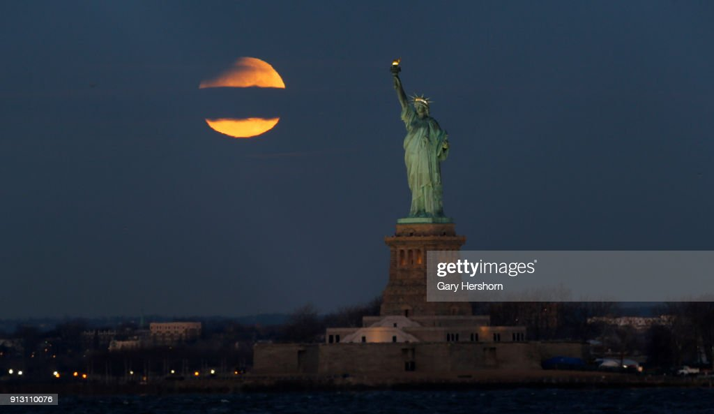 The eclipsed super blue blood moon passes through a cloud as it sets next to the Statue of Liberty at sunsrise on January 30, 2018 in New York City.
