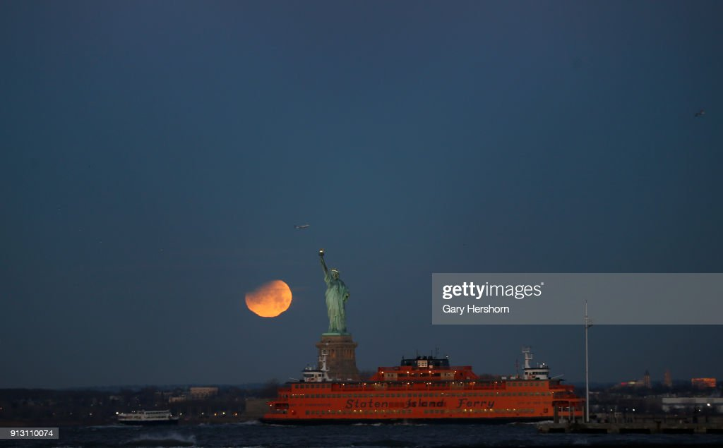 The eclipsed super blue blood moon sets next to the Statue of Liberty at sunrise on January 30, 2018 in New York City.