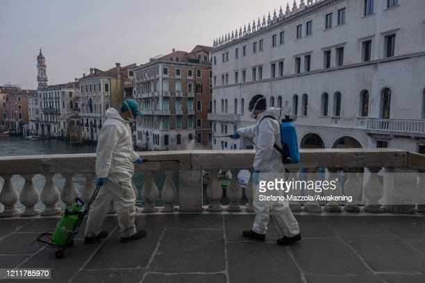 The ecological operator disinfects a marble on the Rialto bridge on March 11 2020 in Venice Italy The Italian Government has taken the unprecedented...