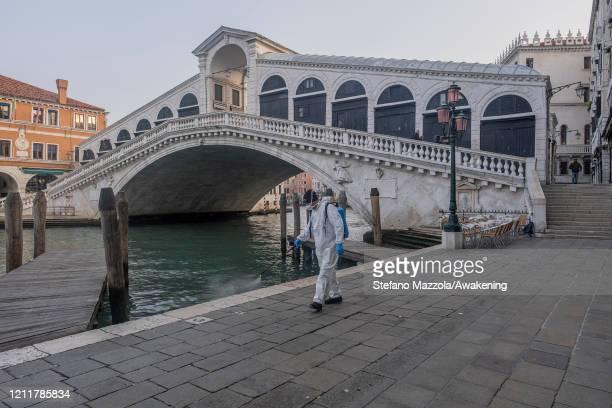 The ecological operator disinfects a shore near the Rialto Bridge on March 11 2020 in Venice Italy The Italian Government has taken the unprecedented...