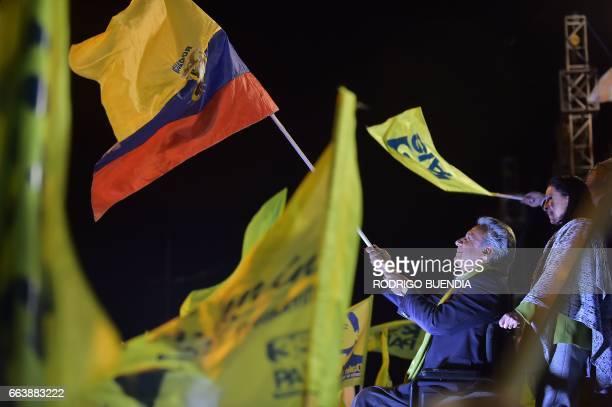 The Ecuadorean presidential candidate of the ruling Alianza PAIS party Lenin Moreno next to his wife Rocio Gonzalez waves the national flag t his...