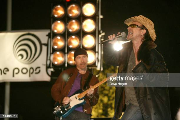 "The Edge and Bono of U2 perform on stage for ""Top Of The Pops"" at BBC Television Centre on October 15, 2004 in London."