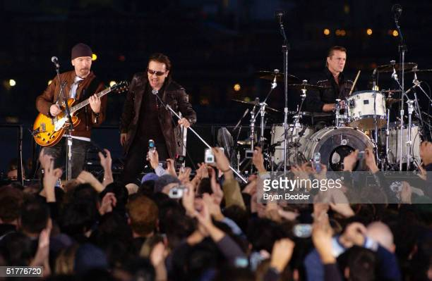 The Edge Bono and Larry Mullen perform with the rock group U2 during the taping of a music video at EmpireFulton Ferry State Park November 22 2004 in...