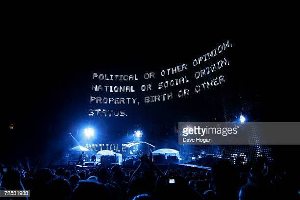 The Edge Bono Larry Mullen Jr and Adam Clayton of U2 perform on stage as graphics related to Make Poverty History are flashed onto the plasma screens...