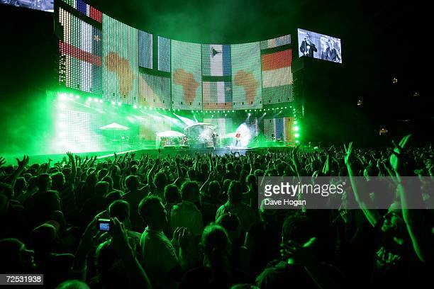 The Edge, Bono, Larry Mullen Jr and Adam Clayton of U2 perform on stage as graphics related to Make Poverty History are flashed onto the plasma...