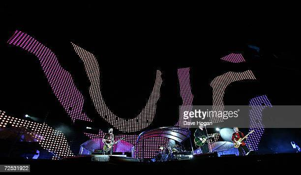 The Edge Larry Mullen Jr Bono and Adam Clayton of U2 perform on stage as aboriginal art is displayed on the plasma screens at the first of three...
