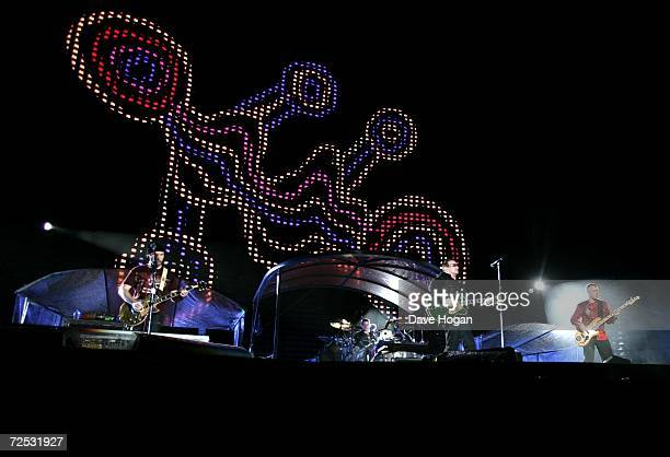 The Edge, Larry Mullen Jr, Bono and Adam Clayton of U2 perform on stage as aboriginal art is displayed on the plasma screens at the first of three...