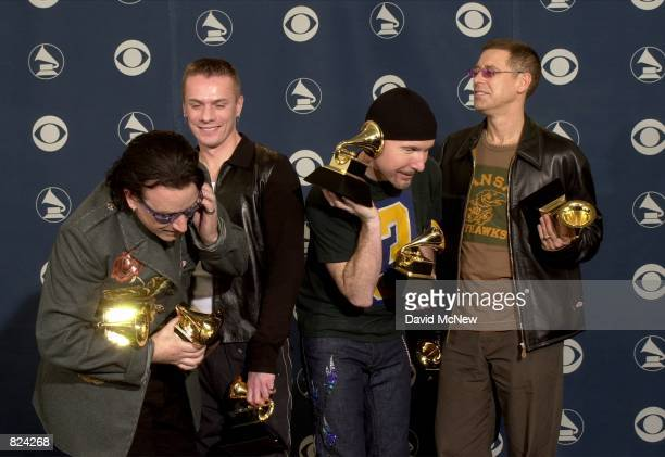 The Edge mimics Bono talking on the mobile phone with his wife while U2 bandmates Larry Mullen Jr 2nd from left and Adam Clayton right look on...