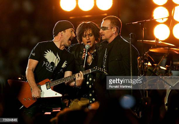 The Edge of U2 Billie Joe Armstrong the lead singer for the rock group Green Day and Bono of U2 perform prior to the Monday Night Football game...