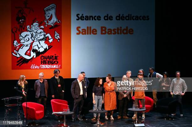The editorial team of Charlie Hebdo newspaper poses for pictures on stage after a discussion about the freedom of the press during a World Forum for...