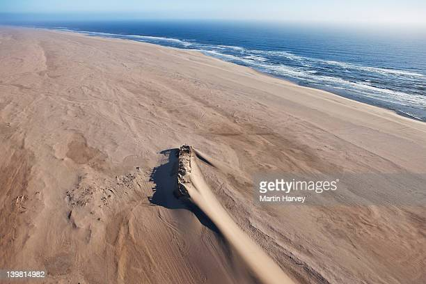 The Eduard Bolhen wreck, a supply ship for the miners that ran aground in 1909. Its steel hull can still be seen and the channel they dug to try and re-float it. Skeleton Coast, Namib desert. Namib-Naukluft National Park, Namibia, Africa