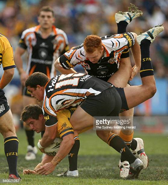 The Eels' Josh Cordoba is tackled by the Tigers' Chris Heighington during the Round 20 NRL rugby league match between the Parramatta Eels and Wests...