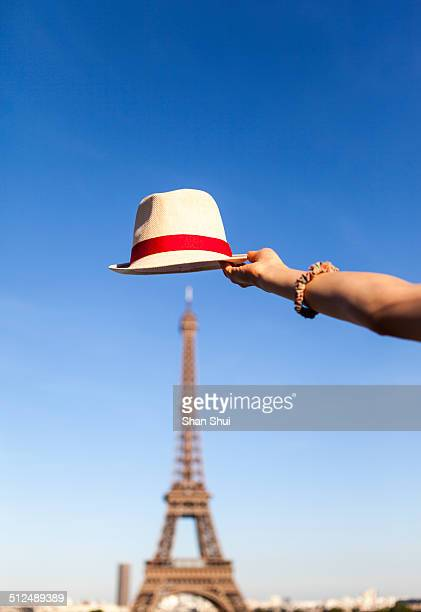The Eiffel Tower and hat in woman hand
