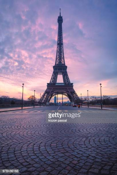 the eiffel tower in paris with paved empty road during a colorful sunrise , france - eiffel tower paris stock pictures, royalty-free photos & images