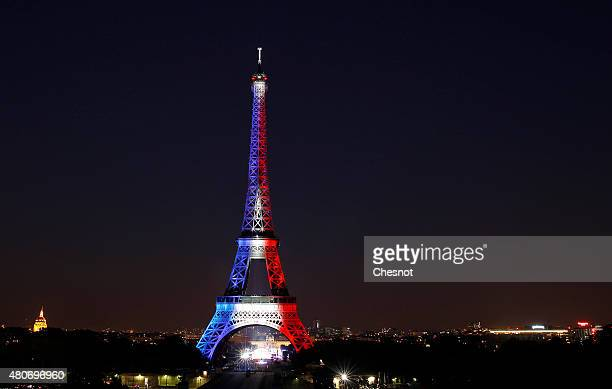 The Eiffel Tower is enlightened with colors of the French national flag prior to the beginning of the fireworks on July 14 2015 as part of France's...