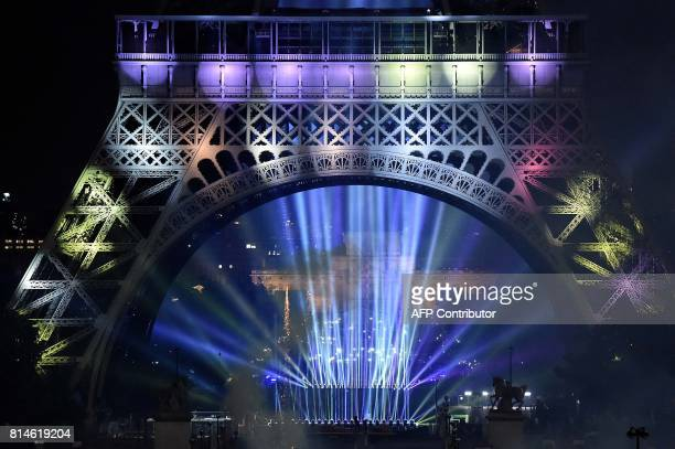 The Eiffel Tower is illuminated at the start of firework show in the French capital Paris on July 14 2017 as part of France's annual Bastille Day...