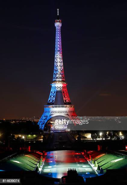 The Eiffel Tower is illuminated in Red White and Blue colors of the French flag prior to a Fireworks as part of Bastille Day celebrations on July 14...