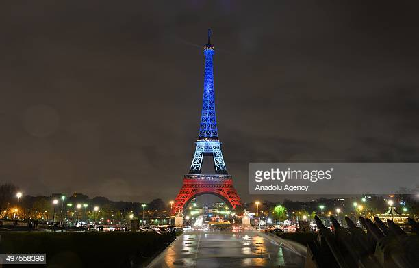 The Eiffel Tower is illuminated in the colors of the French flag to honor victims of Paris attacks on November 17 2015 in Paris France At least 132...