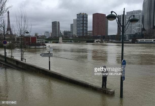 The Eiffel Tower is seen in the background as a man fishes off a barrier partially submerged by the water of the swollen Seine river in Paris on...