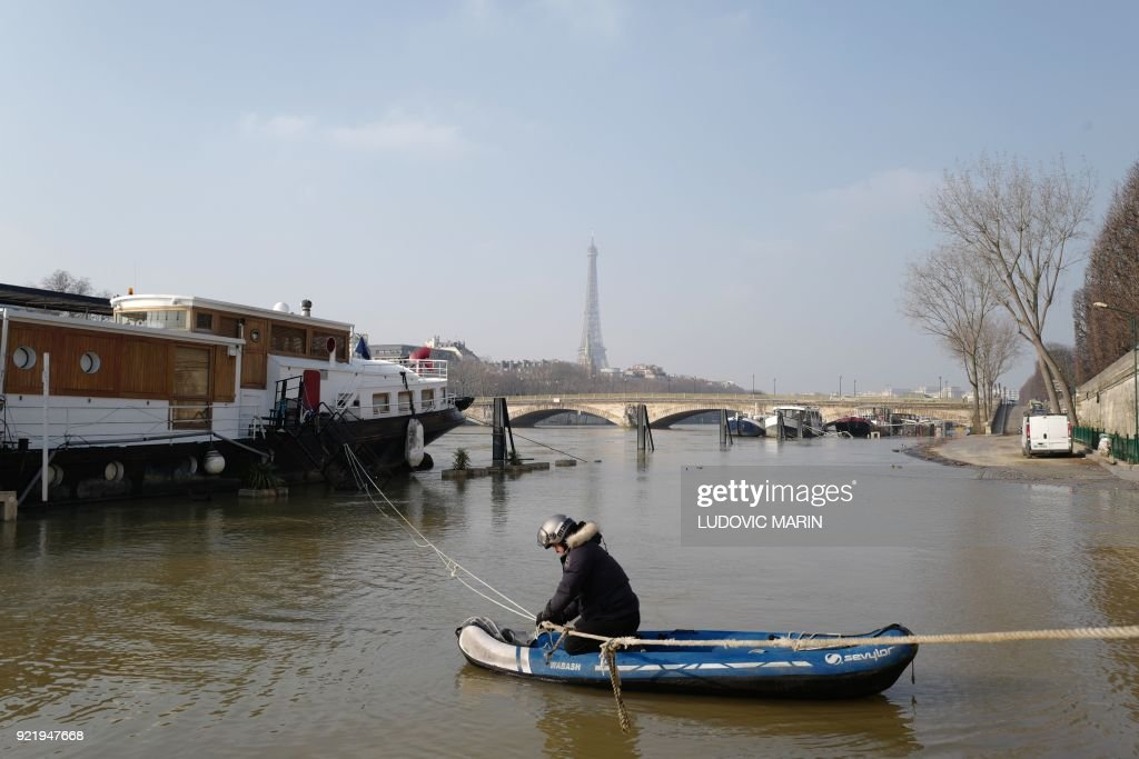 The Eiffel Tower is seen in the background as a man in an inflatable canoe pulls on a rope to check on his boat on the river Seine, the banks of which are still flooded, on February 21, 2018 in Paris. / AFP PHOTO / Ludovic MARIN
