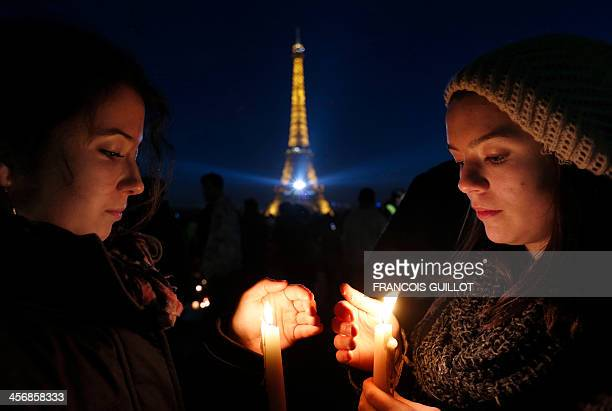 The Eiffel Tower is seen in the distance as people hold candles during a tribute to the late South African President Nelson Mandela on the Parvis des...