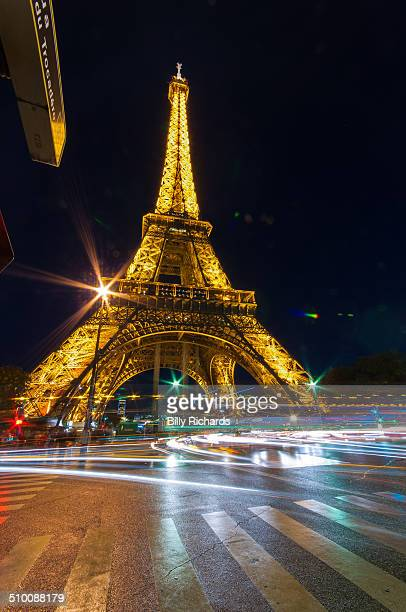 The Eiffel Tower, Paris, France taken at night with light trails from the busy traffic in the foreground.