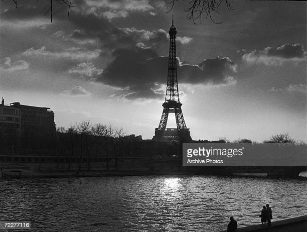 The Eiffel Tower seen from across the Seine at twilight circa 1955
