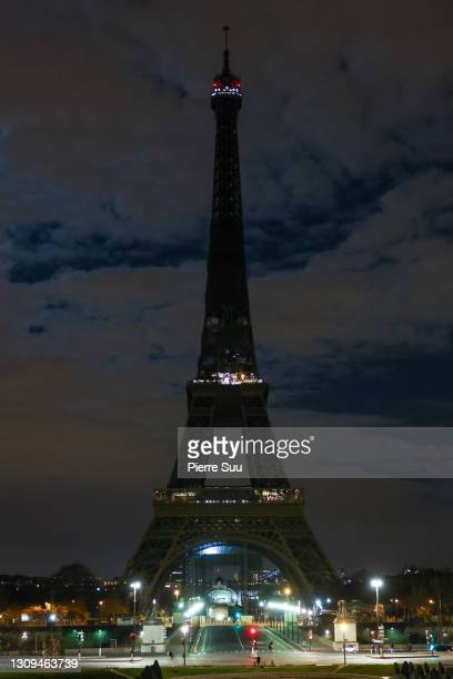 The Eiffel Tower submerges into darkness as part of the Earth Hour switch-off on March 27, 2021 in Paris, France. On the initiative of the World Wide...