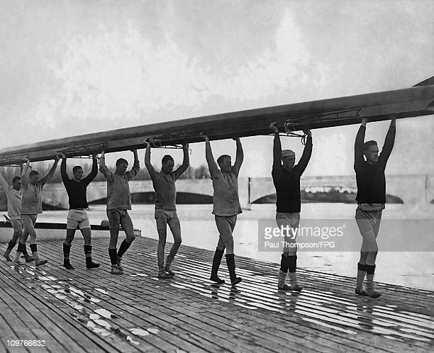 The eight member crew of the Princeton University rowing team carry a rowing boat in 1916