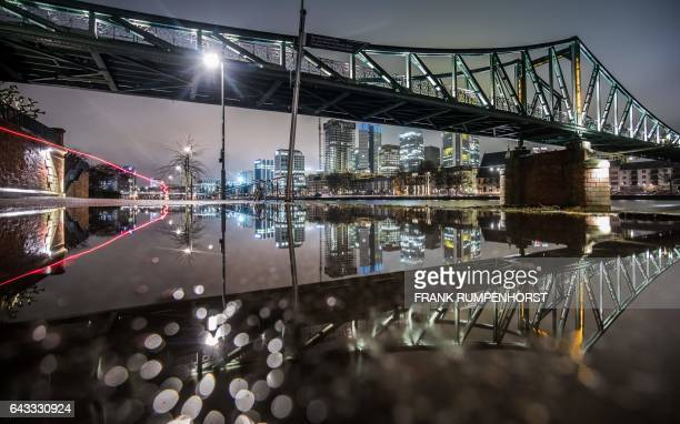 The Eiserner Steg bridge and buildings of Frankfurt's banking district reflect in a puddle as a cyclist draws a red light strip with his rear light...