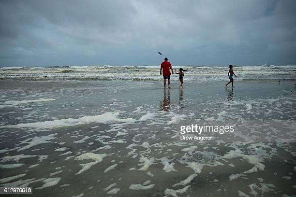 The El Khatib family on vacationing in Florida from Egypt wades into the water along Daytona Beach October 6 2016 in Daytona Beach Florida With...