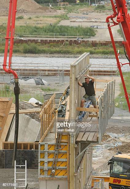 The Elbe River flows behind a worker at the controversial Waldschloesschen Bridge construction site on August 4 2008 in Dresden Germany The bridge...