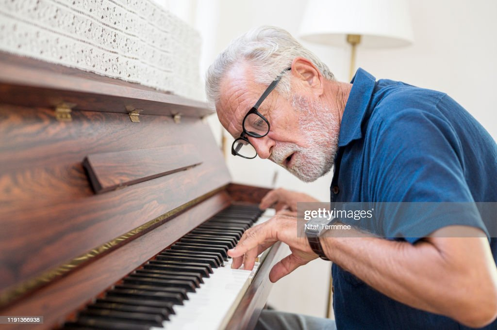 The Elderly man enjoy playing piano at home. : Stock Photo