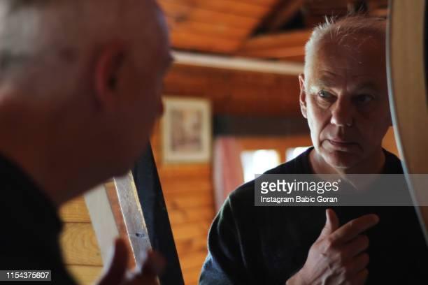 The elderly man is looking in the mirror